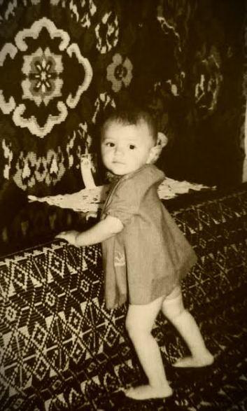 la 11 luni; in fundal, covorul din zestrea mamei, tesut de ea